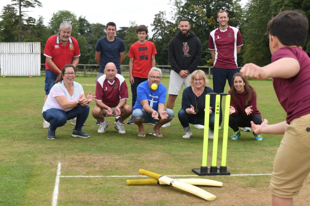 Two rows of people, including young people. In front of them is a wicket and bats. A young person is bowling and an adult in front is reaching out to catch the ball. They are smiling