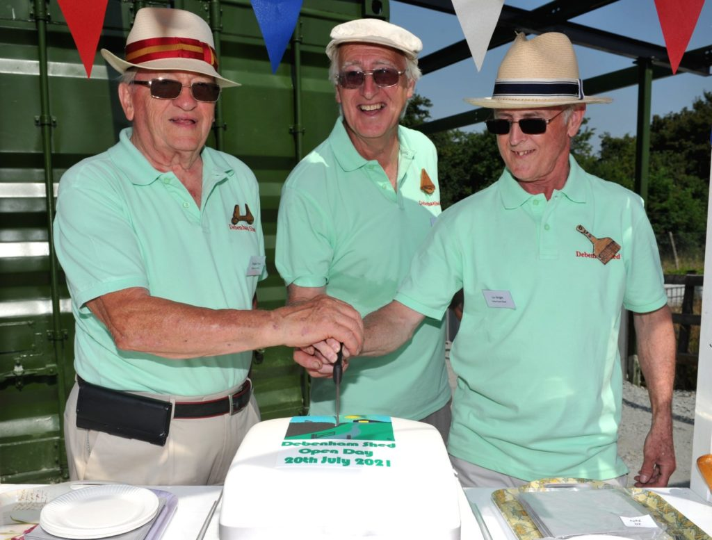 Three members of the shed cut the cake in celebration